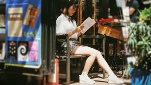 Girl reading book outside shop